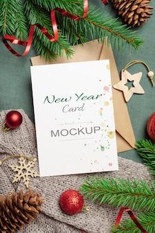 Weihnachts- oder neujahrsgrußkartenmodell mit umschlag und festlicher dekoration mit tannenzweigen