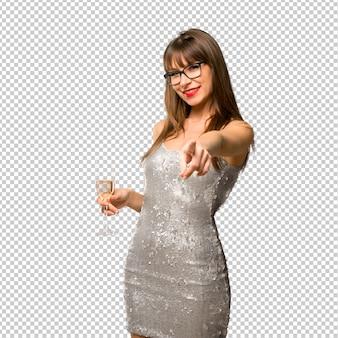 Weihnachtsfeiertage. frau, die ein paillettenbesetztes kleid mit dem champagner feiert neues jahr trägt