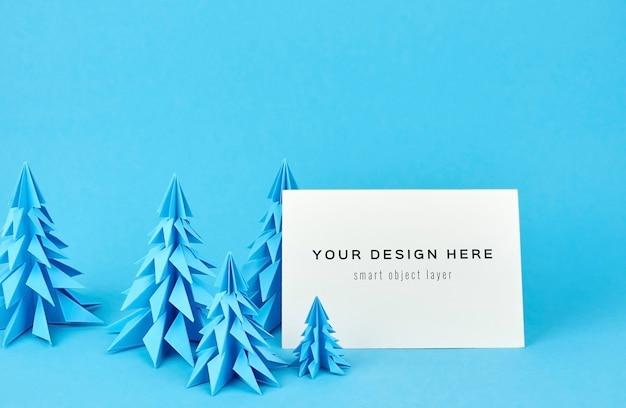 Weihnachtsgrußkartenmodell mit blauen papiertannenbäumen