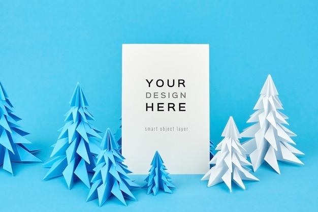 Weihnachtsgrußkartenmodell mit blauen und weißen papiertannenbäumen
