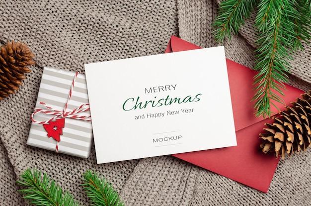 Weihnachtsgrußkartenmodell mit dekorierter geschenkbox, rotem umschlag und tannenzweigen auf gestricktem hintergrund
