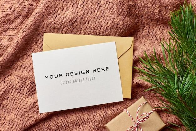Weihnachtsgrußkartenmodell mit geschenkbox auf gestricktem hintergrund