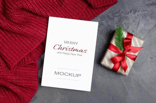 Weihnachtsgrußkartenmodell mit geschenkbox auf rotem gestricktem hintergrund