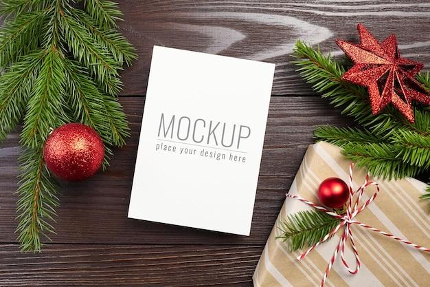 Weihnachtsgrußkartenmodell mit geschenkbox, roter festlicher dekoration und tannenzweigen