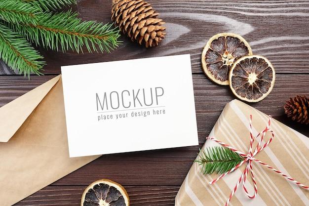 Weihnachtsgrußkartenmodell mit geschenkbox, trockenen orangen, zapfen und tannenzweigen