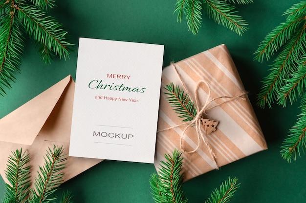 Weihnachtsgrußkartenmodell mit geschenkbox und grünen tannenzweigen