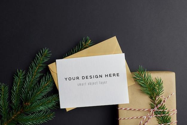 Weihnachtsgrußkartenmodell mit geschenkbox und tannenzweigen auf schwarz