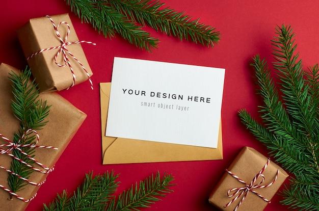 Weihnachtsgrußkartenmodell mit geschenkboxen und kiefernzweigen auf rot