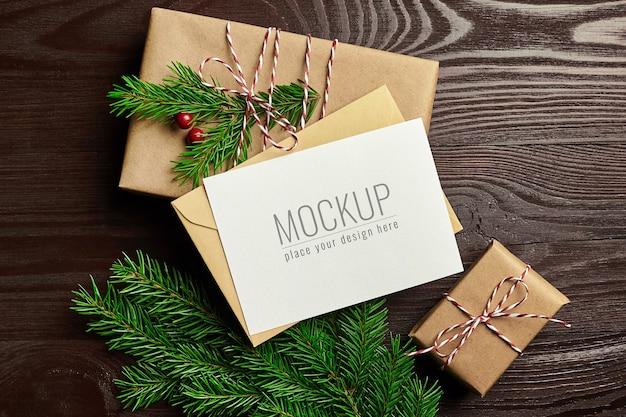Weihnachtsgrußkartenmodell mit geschenkboxen und tannenzweigen auf hölzernem hintergrund