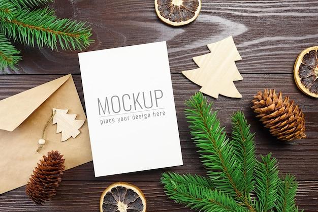 Weihnachtsgrußkartenmodell mit holzdekorationen, zapfen und tannenzweigen