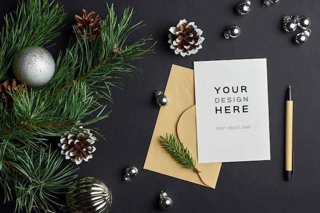 Weihnachtsgrußkartenmodell mit kiefernzweigen und festlichen verzierungen auf dunkelheit