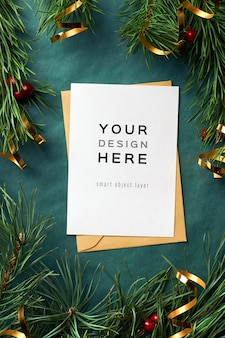 Weihnachtsgrußkartenmodell mit kiefernzweigen und goldbanddekorationen auf grün