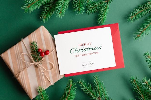 Weihnachtsgrußkartenmodell mit rotem umschlag, geschenkbox und grünen tannenzweigen
