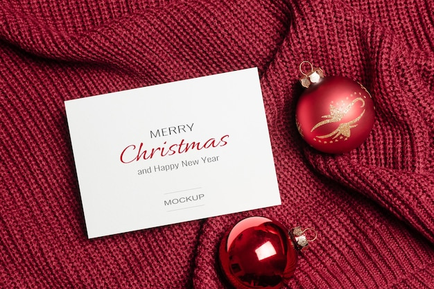Weihnachtsgrußkartenmodell mit roten kugeldekorationen auf gestricktem hintergrund