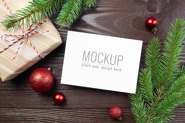 Weihnachtsgrußkartenmodell mit roten kugeln, geschenkbox und tannenzweigen
