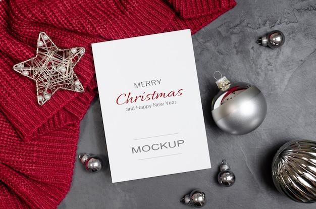 Weihnachtsgrußkartenmodell mit silbernen festlichen dekorationen auf rotem gestricktem hintergrund