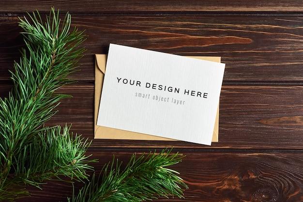 Weihnachtsgrußkartenmodell mit tannenzweigen über hölzernem hintergrund