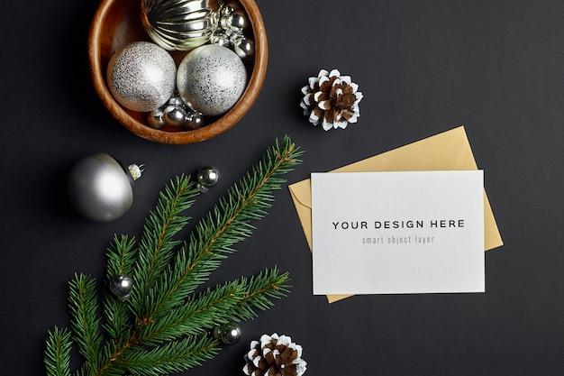 Weihnachtsgrußkartenmodell mit tannenzweigen und festlichen verzierungen auf dunkelheit