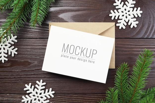 Weihnachtsgrußkartenmodell mit umschlag, weißen schneeflockendekorationen und tannenzweigen