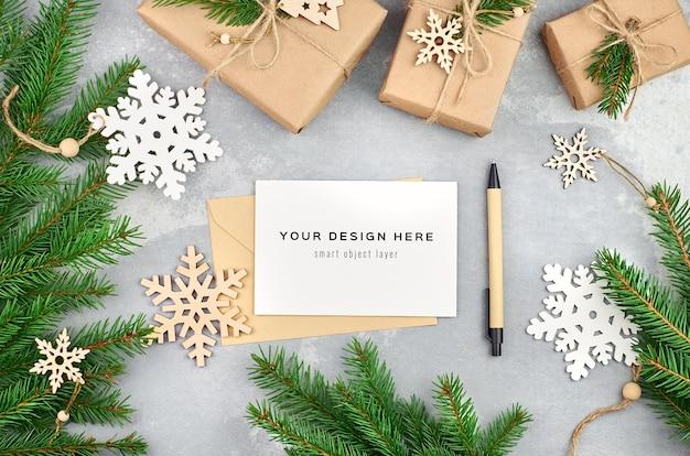 Weihnachtsgrußkartenmodell mit weihnachtsbaumzweigen und -dekorationen