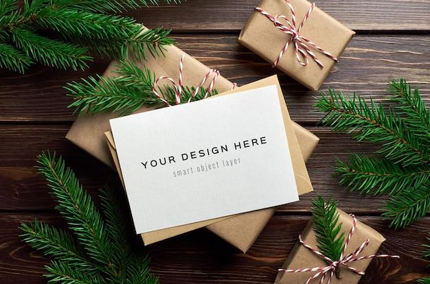 Weihnachtsgrußkartenmodell mit weihnachtsgeschenkboxen und tannenzweigen