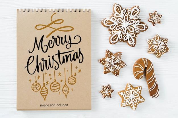 Weihnachtshintergrund mit braunem notizbuchmodell und lebkuchenplätzchen