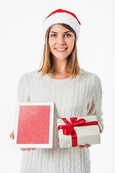 Weihnachtskonzept mit der frau, die tablettenmodell hält