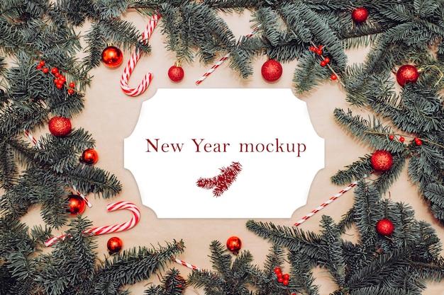 Weihnachtsmodell, postkarte auf dem tisch mit tannenzweigen, roten kugeln, beeren und zuckerstangen