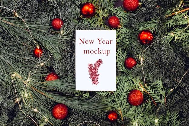 Weihnachtsmodell, weißes blatt papier, das auf fichtenzweigen liegt, rote weihnachtskugeln.