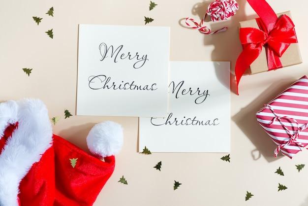 Weihnachtsmodellkarten mit rotem hut und geschenkboxen.