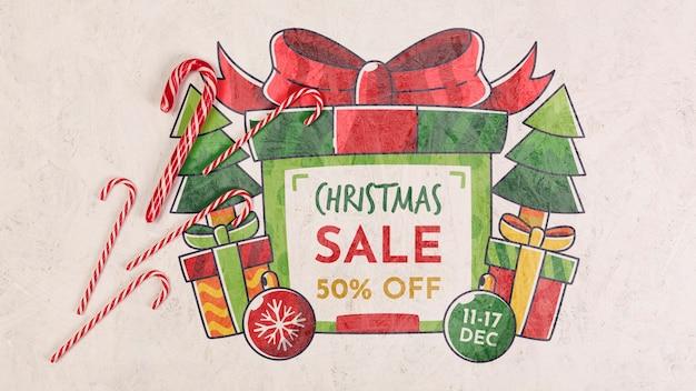 Weihnachtsverkauf mit einer eingewickelten geschenkbox und süßigkeiten