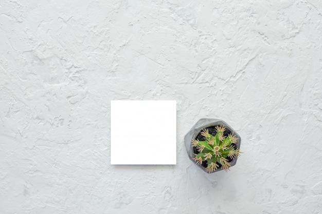 Weiße leere karte auf zementbeschaffenheitshintergrund. attrappe, lehrmodell, simulation