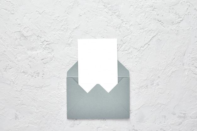 Weiße leere karte im umschlag auf zement