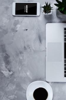 Weißer smartphone mit schwarzem leerem bildschirm auf schreibtisch mit laptop und tasse kaffee