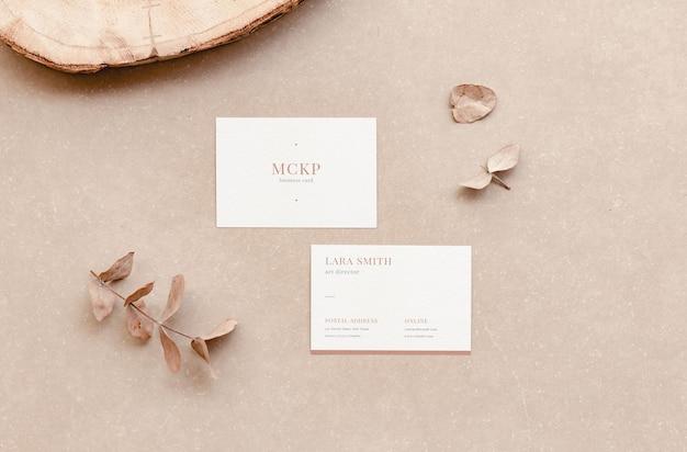 Weißes firmenvisitenkartenmodell für branding-display und natürliche elemente im flat-lay-stil