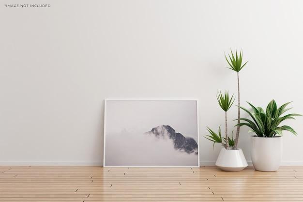 Weißes horizontales fotorahmenmodell auf leerem raum der weißen wand mit pflanzen auf einem holzboden