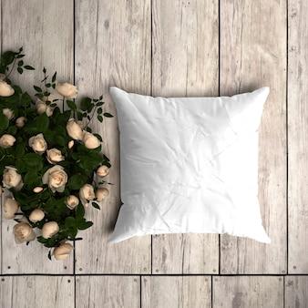 Weißes kissenbezugmodell auf einem holzboden mit dekorativen rosen