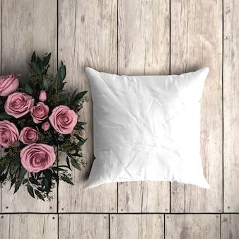 Weißes kissenbezugmodell auf einem holzbrett mit dekorativen rosen