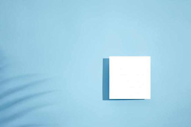 Weißes leeres leeres kartenmodell mit blumenschatten