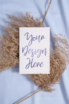 Weißes leeres papierkartenmodell mit trockenem gras der pampa auf blauem neutralem farbigem textil