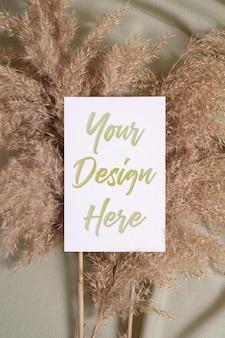 Weißes leeres papierkartenmodell mit trockenem gras der pampa auf einem grünen neutralen textil