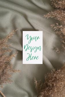 Weißes leeres papierkartenmodell mit trockenem gras der pampa auf grünem textil