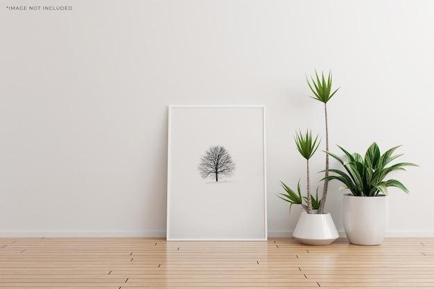Weißes vertikales fotorahmenmodell auf leerem raum der weißen wand mit pflanzen auf einem holzboden