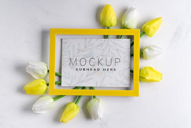 Yellowtulips mit leerem bilderrahmen auf weißem marmorhintergrund, kopienraum
