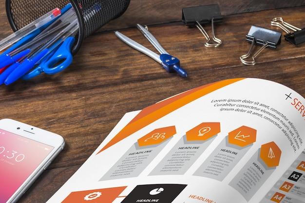Zeitschriften- und smartphonemodell auf holztisch mit stiften und machthabern
