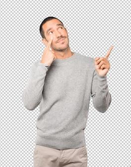 Zögernder junger mann, der eine geste macht, vorsichtig zu sein, wobei seine hand auf sein auge zeigt
