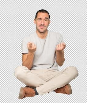 Zögernder junger mann, der mit seinem finger auf dich zeigt