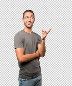 Zögernder junger mann, der mit seinem finger auf sie zeigt