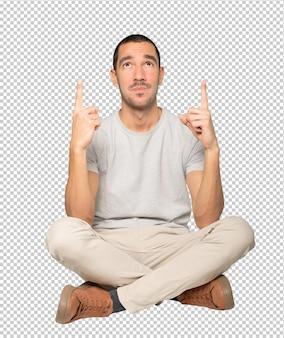 Zögernder junger mann, der mit seinem finger nach oben zeigt