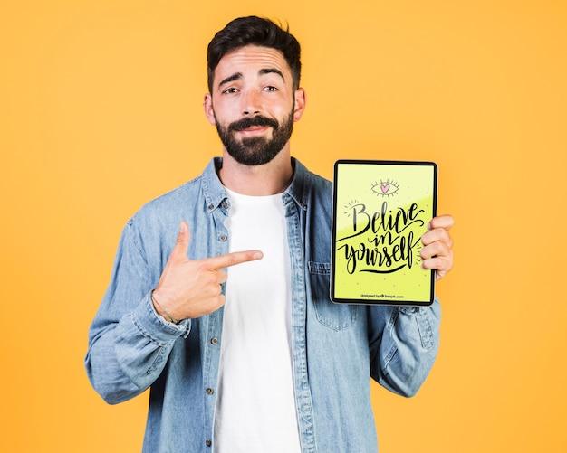Zufälliger junger mann, der oben finger auf einen tablettenspott zeigt